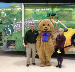 Howard the Bear is flanked by Ivy Tech Chancellor Steve Daily and Library Director Faith Brautigam at unveiling of new bookmobile