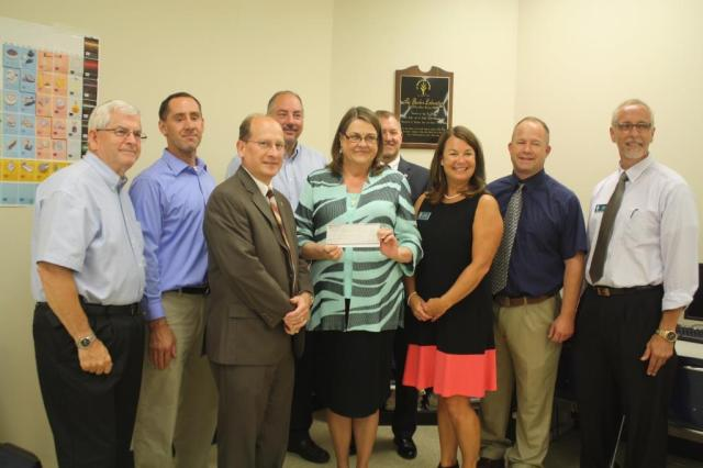 Participating in the check presentation, from left to right, Hal Job, Jay Vandeburg, and Chuck Huffman from Merchant's Trust; Kevin Bostic, Pam Guthrie, John Laws and Kelly Karickhoff from Ivy Tech; Mark Hobbs from Heartland Career Center; and Mike Culver from Ivy Tech.